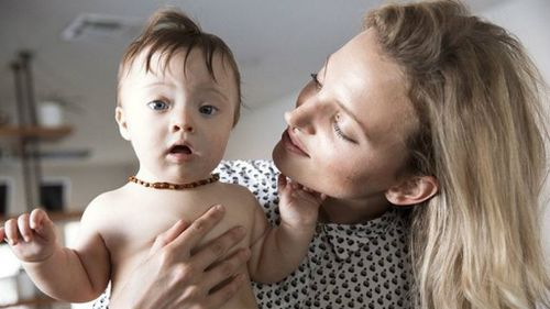 Beautiful baby with Down syndrome loves the camera as much as his model mum