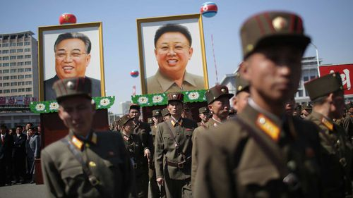 Soldiers carry photos of Kim Il-Sung and Kim Jong-Il during a parade last year. (AAP)