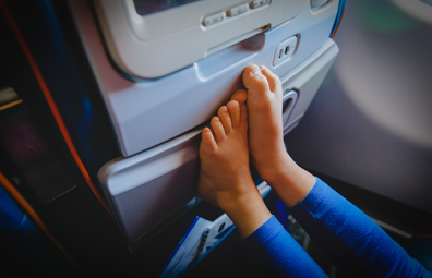 Child in a plane cabin with bare feet, no shoes | Child being annoying on a flight