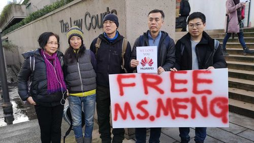 People hold a sign in favor of the release of Huawei Technologies CFO Meng Wanzhou outside the Supreme Court of B.C. during the second day of Meng's bail hearing in Vancouver.