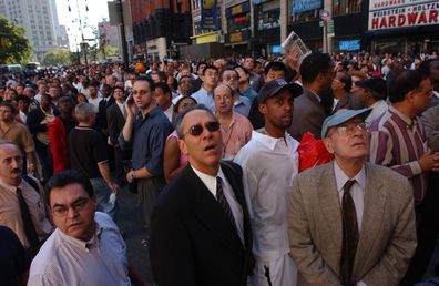 People watch World Trade Center burn on September 11, 2001 after two hijacked airplanes slammed into the twin towers in New York City.
