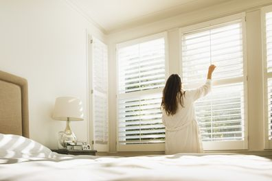 woman opening blinds in bedroom