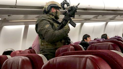 An image purportedly taken on board MH128 shows a heavily armed officer in the aisle. (Supplied)