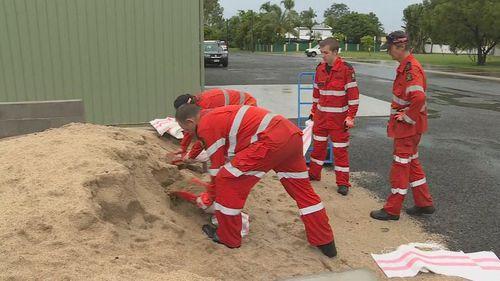 Workers prepare to combat inevitable flooding with sandbags.