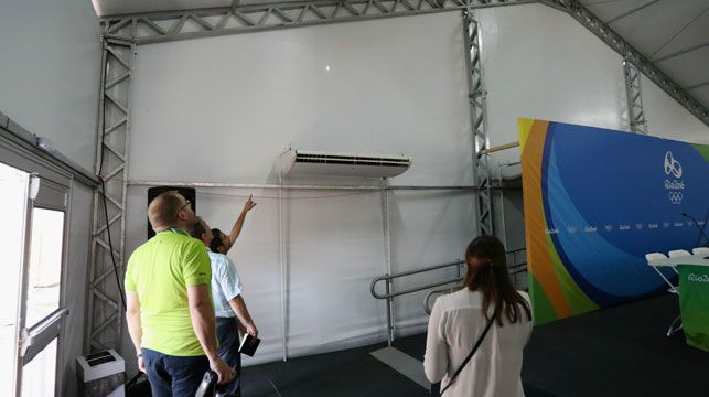 Staff from the Olympic Equestrian Centre's  media room inspect the bullet hole. Photo: Getty