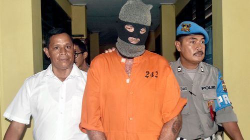 Police officers escort an Australian man identified only as Brandon at police headquarters in Denpasar, Bali. (AAP)