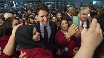 Canada's new prime minister Justin Trudeau personally welcomed 163 Syrian refugees as they entered the country on Thursday. (AAP)