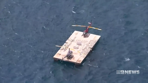 The helicopter floated long enough for the pilot and passengers to be rescued by crews from Hamilton Island. (9NEWS)