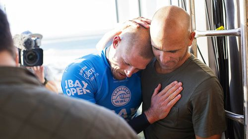 Fanning is comforted by surfing champion Kelly Slater. (AAP)