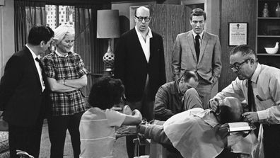 "In this April 11, 1963, file photo, standing from left, Morey Amsterdam, Rose Marie, and Richard Deacon, and Dick Van Dyke, right, gather around Carl Reiner, in barber chair during a rehearsal of an episode for the ""The Dick Van Dyke Show."""