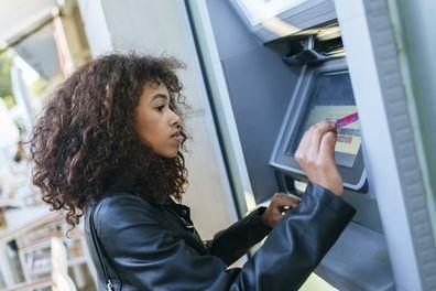 Woman using credit card at ATM