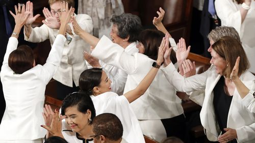 Democrats dressed in white respond during Mr Trump's speech.
