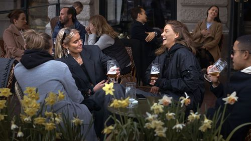 People chat and drink outside a bar in Stockholm, Sweden. Sweden is pursuing relatively liberal policies to fight the coronavirus pandemic.