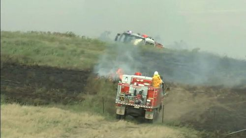 Crews work to contain a grass fire near the Hume Highway, Goulburn.