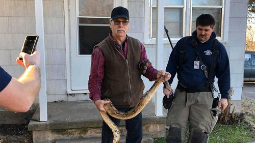 Butler County deputy fire chief Melvin Linot takes the boa constrictor from the house.