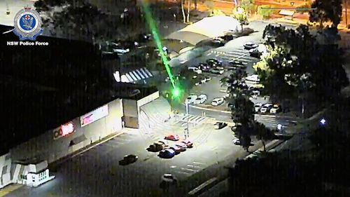 A man with a laser beam shines the powerful light towards a NSW Police chopper.