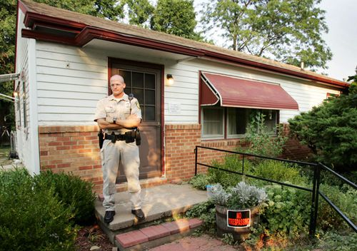 """A Kansas police officer guards the front door of Dennis Rader's home in Park City. Rader, who pleaded guilty last month to killing 10 people in the Wichita area from 1974 to 1991, called himself BTK, for """"Bind, Torture, Kill,"""" in messages to media and police about the crimes. The house was auctioned off for US $90,000 in 2005."""