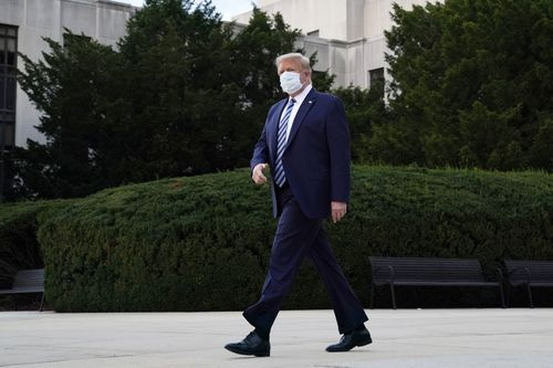 A masked Donald Trump walks out of the hospital this morning.