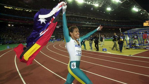 Cathy Freeman walks a lap of honour, carrying the Australian and Aboriginal Flags, after winning Gold in the Womens 400m Finals in 2000. (AAP)
