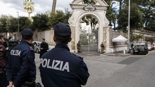 Police officers stand front the entrance of the Apostolic Nunciature in via Po in Rome.