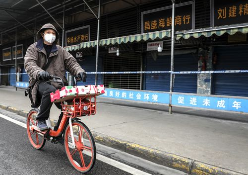 A man wears a mask while riding on mobike past the closed Huanan Seafood Wholesale Market, which has been linked to cases of coronavirus.