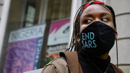 """A woman wearing an """"END SARS"""" protective face mask speaks with the police outside the Nigerian Consulate during a demonstration on October 21, 2020 in London."""