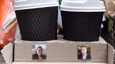 A cardboard tray with two coffee cups shows photos of Katrina Dawson and Tori Johnson - the two hostages killed a fatal siege in the heart of Sydney's financial district - sitting amongst flowers at the makeshift memorial.