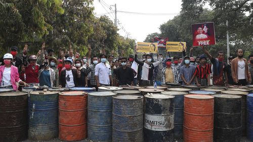 Anti-coup protesters flash the three-fingered salute behind a road barricade made of drums in Mandalay, Myanmar, Saturday, Feb. 20, 2021