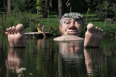 Children sit in the sun by 'The Friendly Giant', a pond sculpture situated in Alnwick Gardens in Anwick, Northumberland, UK.