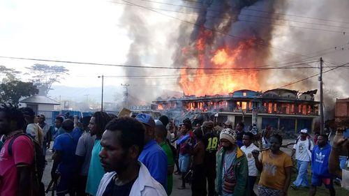 People gather as shops burn in Wamena