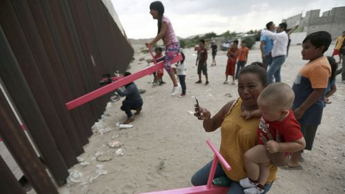 Families on the Mexico side of the border play on a see-saw.