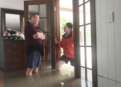 Amelia Rankin checks on her neighbour Adam Hanson in Hermit Park, Townsville, Monday, February 4, 2019. The line on the wall at the right shows the water level reached overnight.