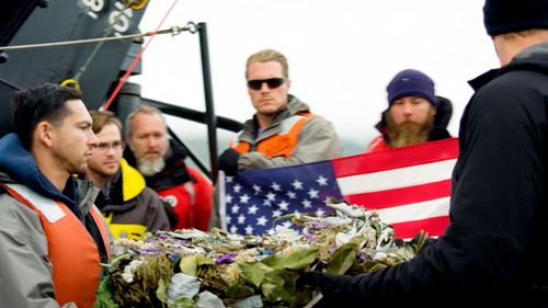 Project Recover, crew members prepare to place a wreath over the wreckage of the stern of the destroyer USS Abner Read.