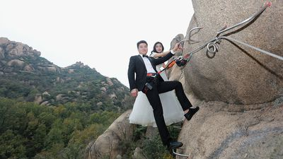 Adventurous newlyweds pose for wedding photos on cliff face
