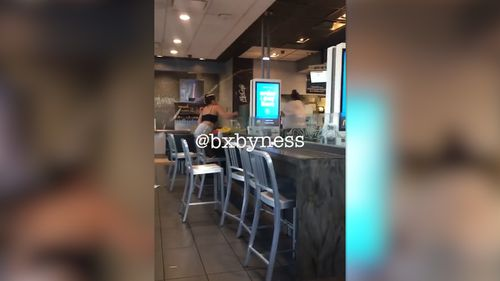 The video shows a shoeless woman wearing figure-hugging shorts and a crop top seated with her meal, yelling across the restaurant at someone off camera. Picture: Facebook/Marie Dayag