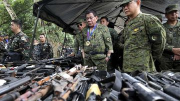 Rodrigo Duterte looks at weapons seized by Islamist extremists in Marawi. (AAP)