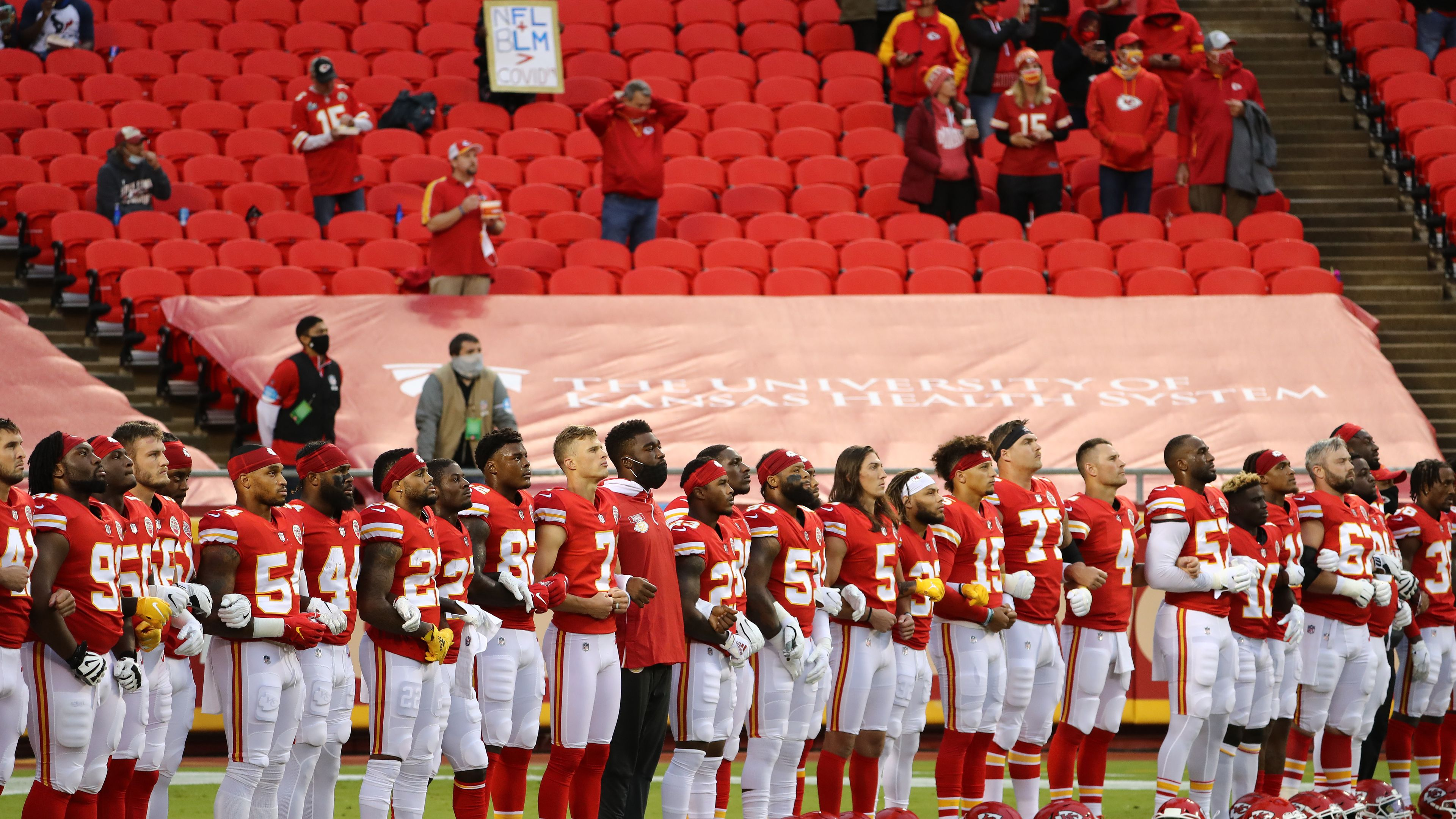Members of the Kansas City Chiefs stand united with locked arms.