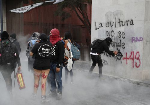 Demonstrators deface a wall along the way of a protest for 43 missing teachers' college students, on the fifth anniversary of their disappearance, in Mexico City. Groups of masked demonstrators flying anarchists flags and dressed in black broke windows and defaced walls, on the tail end of the peaceful protest which was led by relatives and friends of the missing students.