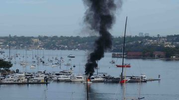 A reader image of the boat on fire at the marina in Drummoyne.