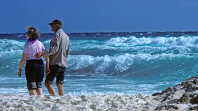 Couple walking on beach retirement