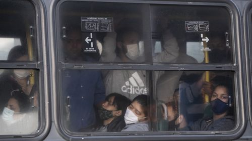 Commuters crowd a bus during the COVID-19 pandemic in Rio de Janeiro.