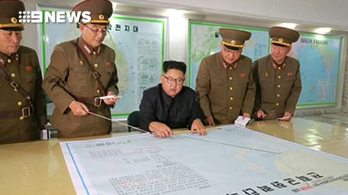 North Korean leader Kim Jong-un is seen reviewing a plan for an attack on Guam.
