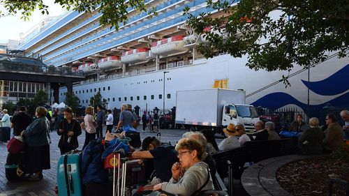 Passengers sit with their luggage after disembarking from the Ruby Princess cruise ship at the Overseas Passenger Terminal in Circular Quay, Sydney.