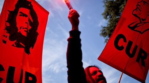 "Chileans hold banners depicting ""Che"" Guevara"" and Jose Marti. (AP)."