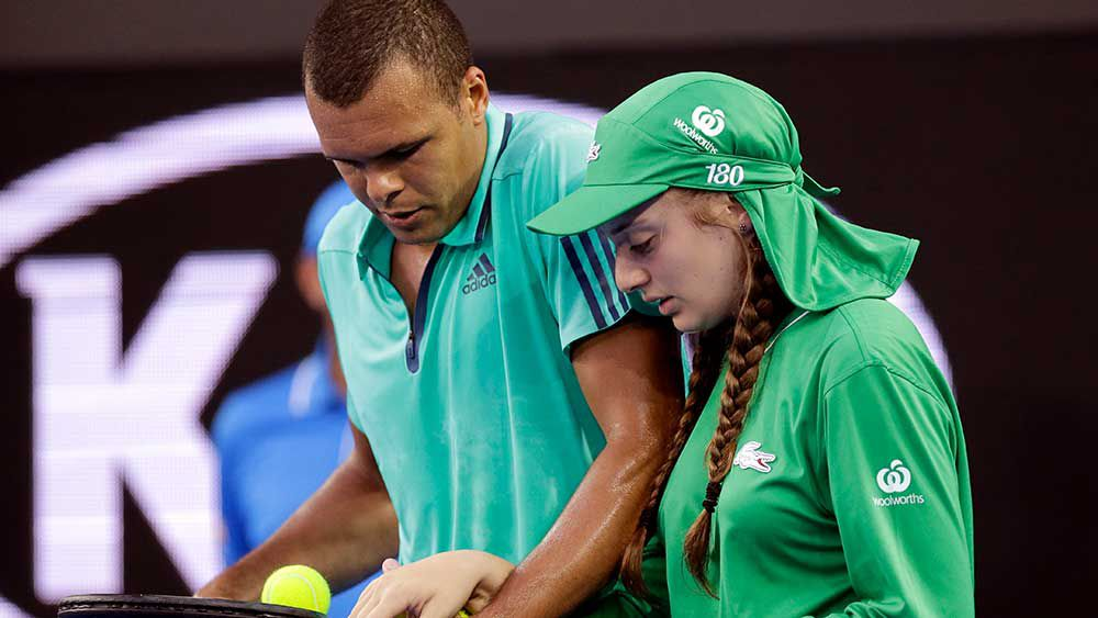 Jo-Wilfried Tsonga helps out an injured ball-girl during the 2016 Australian Open. (AAP)