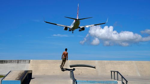 A skateboarder looks on as a Virgin commercial aircraft from Sydney lands at the Gold Coast Airport in March, 2020.