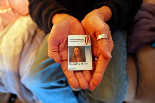 Kim Mincks shows an identification card of her housemate Elizabeth Theriot.
