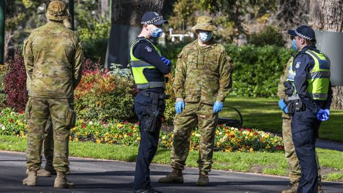 Australian Defence Force staff (ADF) and Victorian police are seen on patrol as a lockdown of Melbourne forces people to stay at home if not working, providing care or buying groceries.