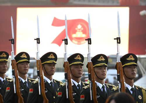 Members of a Chinese military honour guard stand at attention during a rehearsal before a large parade to commemorate the 70th anniversary of the founding of Communist China in Beijing.