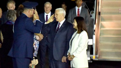 An official salutes US Vice President Mike Pence and his wife Karen on the tarmac in Cairns, Queensland.